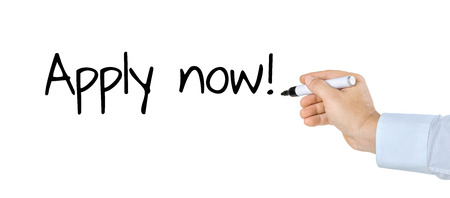 headhunter: Hand with pen writing Apply now Stock Photo