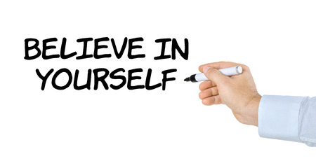 text marker: Hand with pen writing Believe in yourself Stock Photo