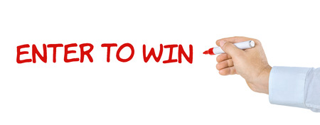 sweepstake: Hand with pen writing Enter to win Stock Photo