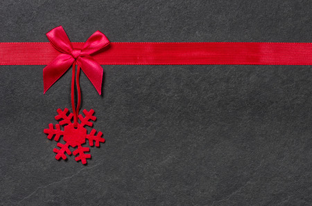 black ribbon bow: Slate board with a felt snowflake Stock Photo