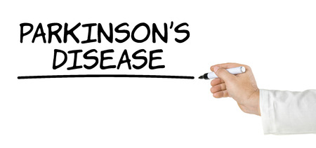 parkinsons: Hand with pen writing Parkinsons Disease