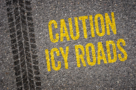 Lane with the text Caution icy roads Stock Photo