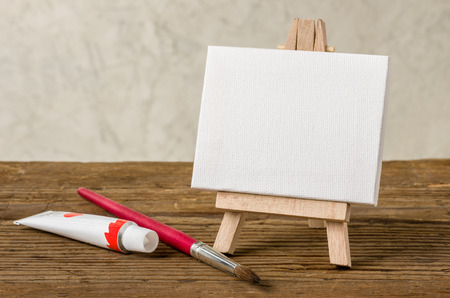 blank canvas: Easel with a blank canvas, paint and brush Stock Photo