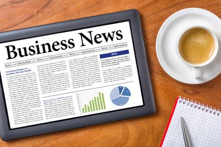 Tablet op een bureau - Business News Stockfoto