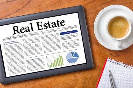 periódicos: Tablet en un escritorio - Real Estate Foto de archivo