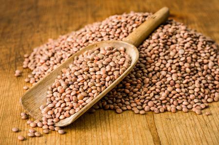 wooden scoop: Wooden scoop with brown lentils