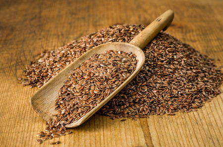 flax seeds: Wooden scoop with flax seeds Stock Photo
