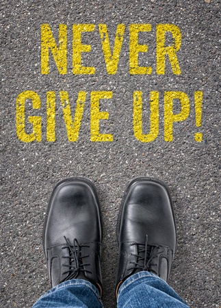 give way: Text on the floor - Never give up Stock Photo