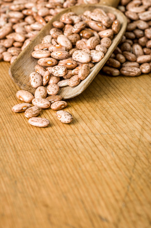 Wooden background with copy space - Pinto beans photo