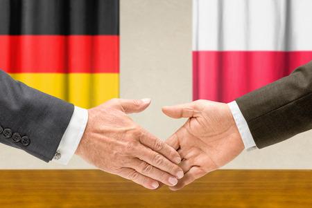 poland flag: Representatives of Germany and Poland shake hands
