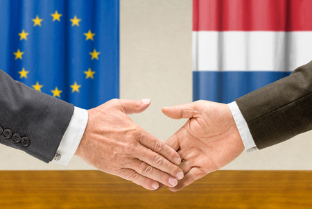 Representatives of the EU and the Netherlands shake hands photo
