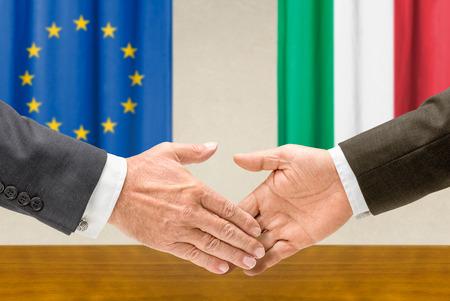 Representatives of the EU and Italy shake hands photo