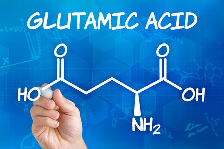 chemical formula: Hand with pen drawing the chemical formula of glutamic acid