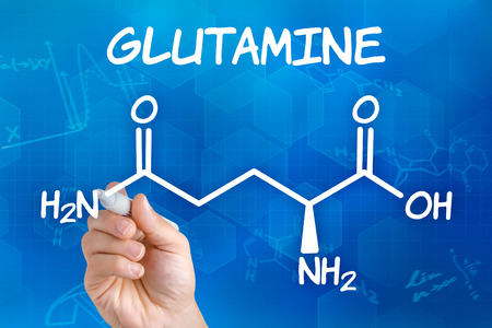 Hand with pen drawing the chemical formula of glutamine photo