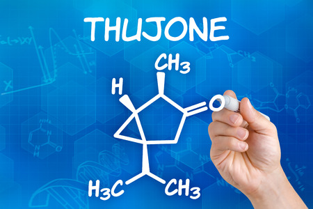chemical formula: Hand with pen drawing the chemical formula of thujone Stock Photo