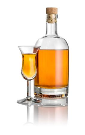 琥珀色の液体で満たされたボトルと高い茎のガラス
