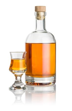 Flasche und Schnapsglas mit bernsteinfarbenen Flüssigkeit gefüllt Standard-Bild