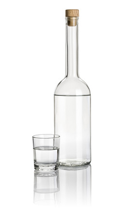 liquor bottle: Liquor bottle and drinking glass filled with clear liquid