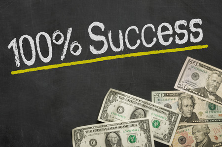 financial diversification: Text on blackboard with money - 100 percent success