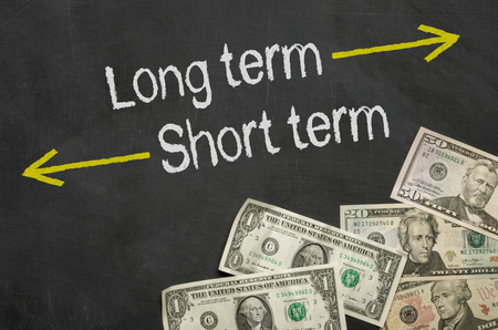 investing: Text on blackboard with money - Long term and short term Stock Photo