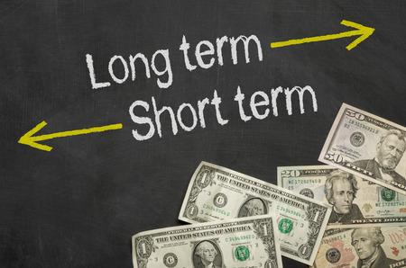 Text on blackboard with money - Long term and short term Foto de archivo