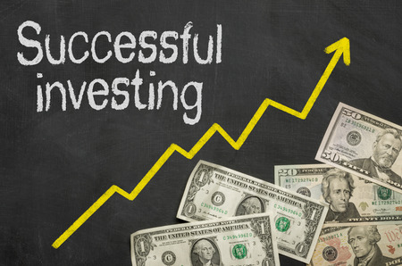 investing: Text on blackboard with money - Successful investing