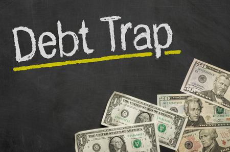 debt trap: Text on blackboard with money - Debt Trap