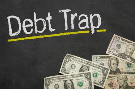 debt trap: Text on blackboard with money - Debt Trap