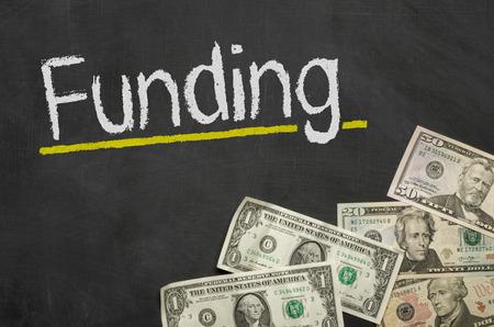 Text on blackboard with money - Funding photo