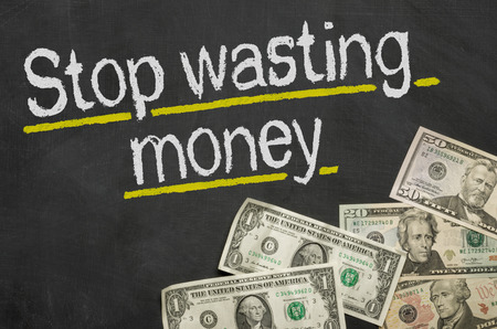 wasting: Text on blackboard with money - Stop wasting money Stock Photo