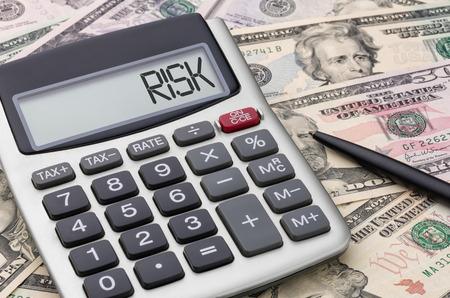 negative returns: Calculator with money - Risk Stock Photo