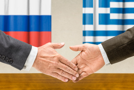greece flag: Representatives of Russia and Greece shake hands Stock Photo