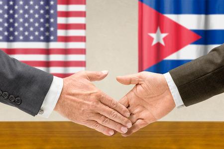 cuba flag: Representatives of the United States and Cuba shake hands