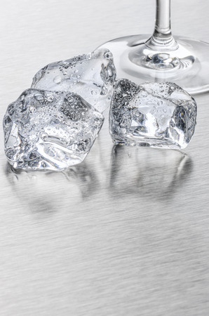 ice sheet: Ice cubes and cocktail glass on a metallic surface