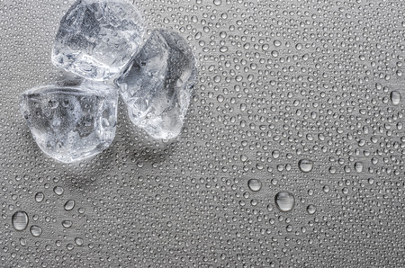 Ice cubes on a metallic surface with droplets Stock Photo