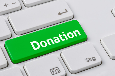 A keyboard with a green button - Donation Foto de archivo