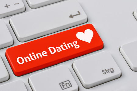 dating and romance: A keyboard with a red button - Online Dating