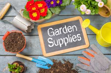 watering garden: Blackboard on a plant table with garden tools - Garden Supplies Stock Photo