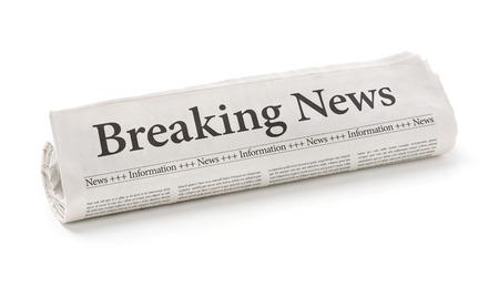 Rolled newspaper with the headline Breaking news Foto de archivo