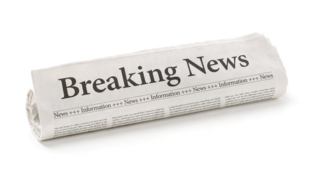 breaking news: Rolled newspaper with the headline Breaking news Stock Photo