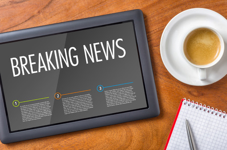 Tablet op een houten bureau - Breaking News Stockfoto
