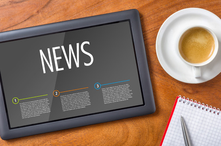 latest: Tablet on a wooden desk - News Stock Photo