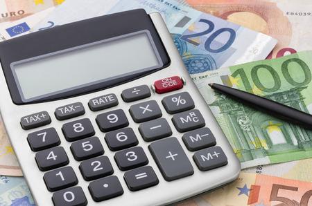 calculation: Calculator with euro bills Stock Photo