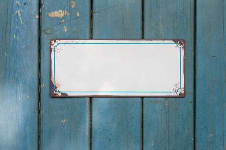 sign plate: Empty metal sign in front of a wooden wall