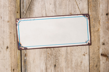 Empty metal sign in front of a rustic wooden wall