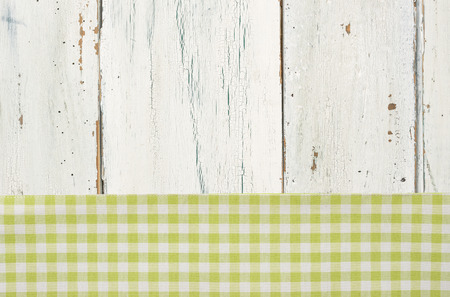 menue: Green checkered tablecloth on a white wooden background