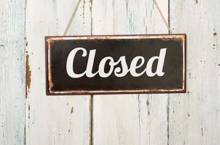 closed sign: Old metal sign in front of a white wooden wall - Closed