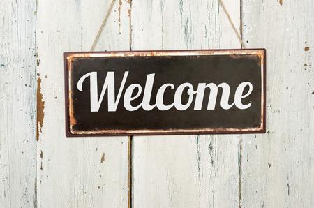the welcome: Letrero de metal viejo delante de una pared de madera blanca - Bienvenido Foto de archivo