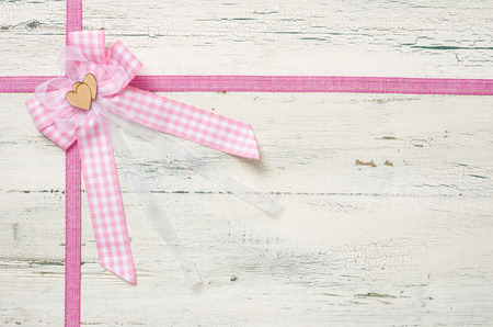 Pink ribbons and a bow on a white wooden background photo