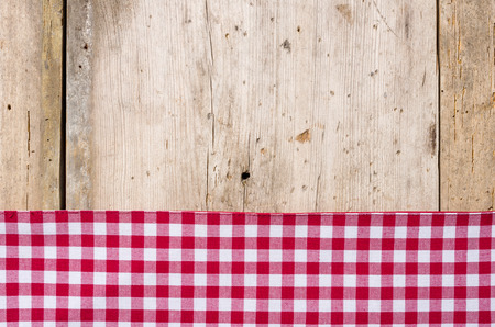 menue: Red checkered tablecloth on a rustic wooden background